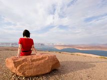 Singelkvinna som framme mediterar av en lake Royaltyfria Bilder