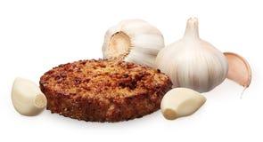 Singeln grillade hamburgaren och ny vitlök med kryddnejlikor på vit Royaltyfria Bilder