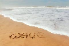 Singeln uttrycker vinkar skriftligt på sanden Arkivbilder