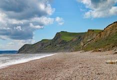Singelstranden på Eype i Dorset på en solig dag, sandstenklipporna av den Jurassic kusten kan ses i bakgrunden arkivbilder