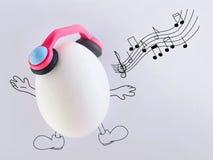 Singen Sie ein Lied glücklich, frische Eier in den Kopfhörern Lizenzfreies Stockfoto
