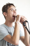 The singer. The young guy sings in a microphone on a white background Stock Photo