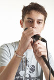 The singer. The young guy sings in a microphone on a white background Stock Image