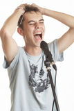 The singer. The young guy sings in a microphone on a white background Stock Images