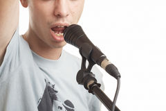 The singer. The young guy sings in a microphone on a white background royalty free stock images