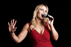 Singer. A beautiful singer in a red dress with a microphone on a black background Stock Photos