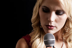 Singer. A beautiful singer with microphone on a black background Stock Photography