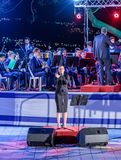 The singer, accompanied by a brass band, performs a song at a commemorative ceremony in the Memorial Site To the Fallen in Israel. Nahariyya, Israel, April 17 stock images