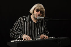Singer accompanying himself on electric piano. Bearded grey haired singer accompanying himself on electric piano on black background Royalty Free Stock Image