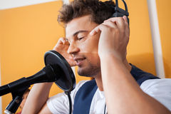 Singer Adjusting Headphones While Singing In Recording Studio. Young male singer adjusting headphones while singing in recording studio Royalty Free Stock Image