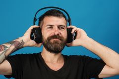 Singer with beard and smiling face enjoys music. stock photography