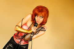 Singer. Beautiful red-haired girl with microphone in her hand Royalty Free Stock Image