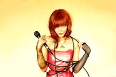 Singer. Beautiful red-haired girl with microphone in her hand Stock Photo