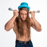 Singer bodybuilder shirtless with long hair in a blue hat with a microphone Royalty Free Stock Photography