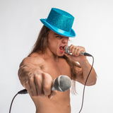Singer bodybuilder shirtless with long hair in a blue hat with a microphone Stock Image