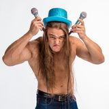 Singer bodybuilder shirtless with long hair in a blue hat with a microphone Stock Photos