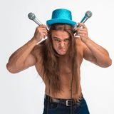 Singer bodybuilder shirtless with long hair in a blue hat with a microphone Royalty Free Stock Photo