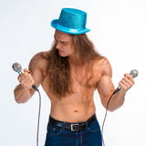 Singer bodybuilder shirtless with long hair in a blue hat with a microphone Royalty Free Stock Images