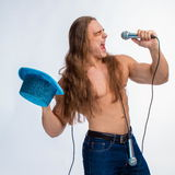 Singer bodybuilder shirtless with long hair in a blue hat with a microphone Stock Images