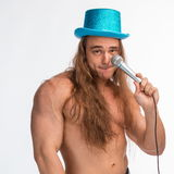 Singer bodybuilder shirtless with long hair in a blue hat with a microphone Stock Photography