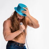 Singer bodybuilder shirtless with long hair in a blue hat with a microphone Royalty Free Stock Image
