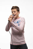 Singer brunette boy in a pink jumper with a microphone and headphones. On a white background Royalty Free Stock Photo