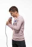 Singer brunette boy in a pink jumper with a microphone and headphones. On a white background Royalty Free Stock Image