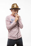 Singer brunette boy in a pink jumper with a microphone and headphones. On a white background Stock Image