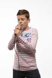 Singer brunette boy in a pink jumper with a microphone. On a white background royalty free stock image