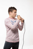 Singer brunette teenager boy in a pink jersey in gold hat with a microphone. On a white background Stock Photos