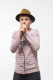 Singer brunette teenager boy in a pink jersey in gold hat with a microphone. On a white background Stock Photo