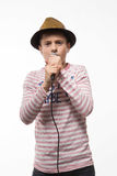 Singer brunette teenager boy in a pink jersey in gold hat with a microphone. On a white background Royalty Free Stock Image