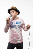 Singer brunette teenager boy in a pink jersey in gold hat with a microphone. On a white background Royalty Free Stock Photography