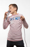 Singer brunette teenager boy in a pink jumper with a microphone Royalty Free Stock Images