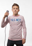 Singer brunette teenager boy in a pink jumper with a microphone. On a white background Stock Image