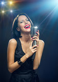 Singer with closed eyes keeping mic on illuminated background. Half-length portrait of female musician with closed eyes wearing black evening dress and keeping Stock Photography
