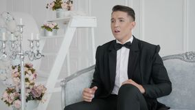 Singer sings in luxury room. Singer in costume sings against the backdrop of a bright and luxury room in a retro style. Young man in suit stock footage