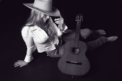 Singer with a cowoy hat and Guitar. Shot of a sexy girl with a guitar and a cowboy hat Royalty Free Stock Photography