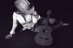 Singer with a cowoy hat and Guitar. Shot of a girl with a guitar and a cowboy hat royalty free stock photo