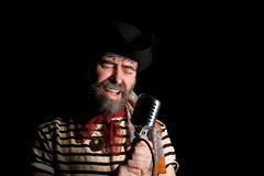 Singer dressed as sea pirate. Sings in an old microphone Royalty Free Stock Photography