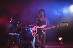 Singer and drummer performing in illuminated nightclub. Confident singer and drummer performing in illuminated nightclub Stock Photography