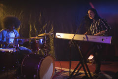 Singer and drummer performing in illuminated nightclub Stock Images
