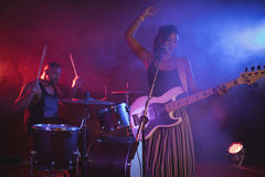 Singer and drummer performing in nightclub. Singer and drummer performing in illuminated nightclub Stock Images
