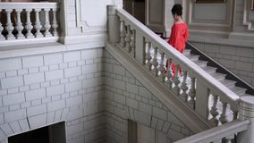 Singer in elegant red dress on high heels climbs a large staircase at beautiful hall