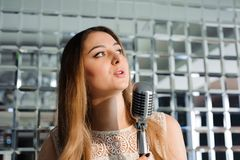 Singer in front of a microphone in a karaoke club. stock photography
