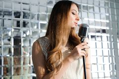 Rock star. Girl singing in retro microphone royalty free stock photo