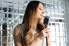 Singer in front of a microphone in the club. royalty free stock photos