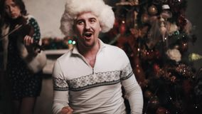 Singer in fur hat performing with string quartet sitting near christmas tree. Unshaved caucasian joyful singer in white fur hat performing with string quartet stock video footage