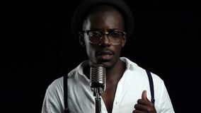Singer gesticulating sings into a retro microphone and dancing near it. Black background. Slow motion. Close up stock footage