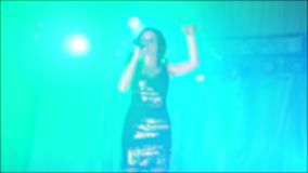 Singer girl brunette sings blurred concert night beautiful light with microphone. slow motion video. Singer in stock footage